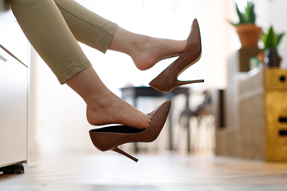 Tired woman resting with feet taking off brown high heeled shoes after work or walk at home, lying down on sofa, blurred background. Foot fatigue, discomfort shoes concept