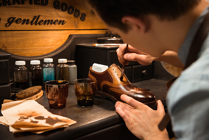 Side view image of young concentrated shoemaker in workshop making shoes. Looking aside.